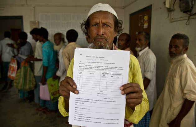 Kismat Ali, whose wife's name did not appear on the NRC draft, shows a form he collected to file an appeal...