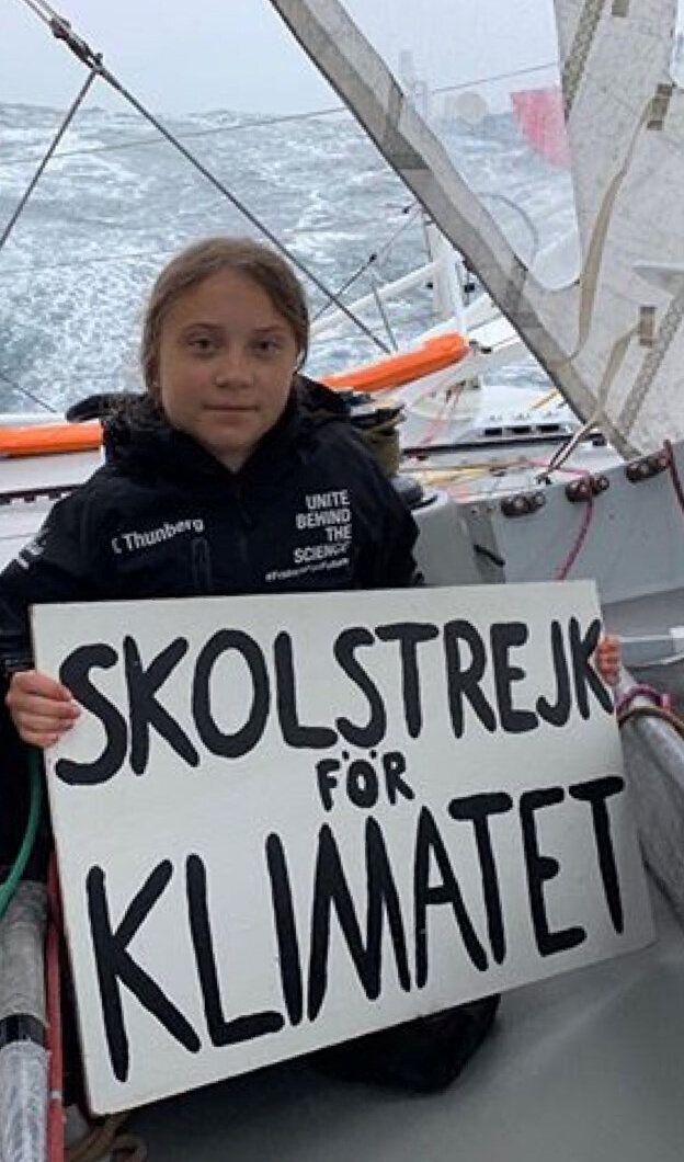 Greta Thunberg à bord du Malizia II avec un panneau affichant