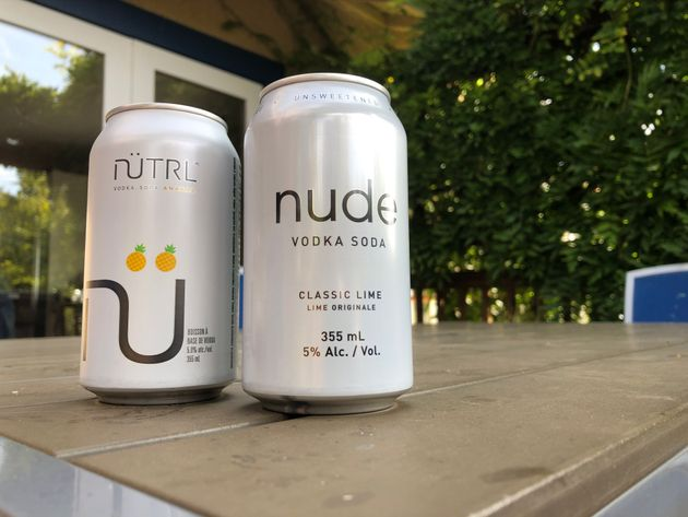 Two different vodka soda cans from brands Nütrl and Nude are pictured on an outdoor
