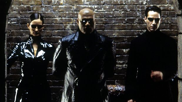 Carrie-Anne, Moss Laurence Fishburne, and Keanu Reeves standing against brick wall in a scene from the film 'The Matrix Reloaded', 2003. (Photo by Warner Brothers/Getty Images)