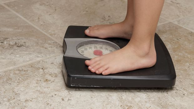 young girls feet on a set of bathroom scales
