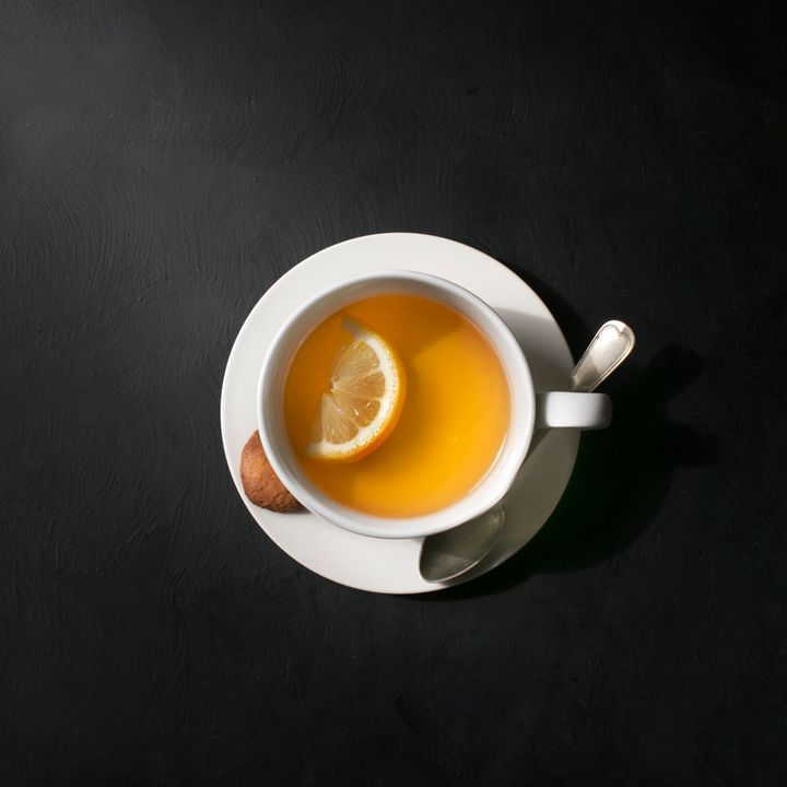 Overhead view of a white cup with lemon tea. Rustic moody black background.