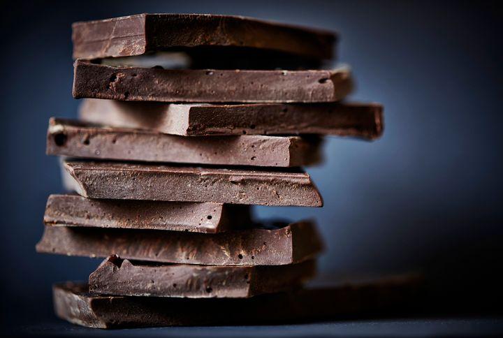 Chocolate broken on a stack, on a dark background.