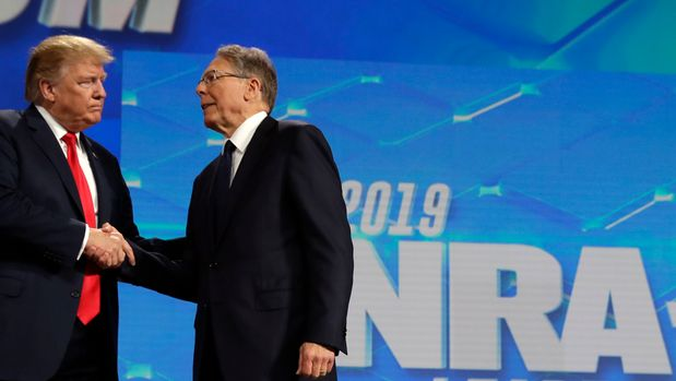 President Donald Trump shakes hands with NRA executive vice president and CEO Wayne LaPierre, has he arrives to speak to the annual meeting of the National Rifle Association, Friday, April 26, 2019, in Indianapolis. (AP Photo/Evan Vucci)