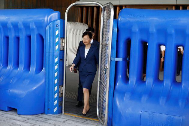 집무실을 둘러싼 플라스틱 바리케이드 사이로 캐리 람 홍콩 행정장관이 모습을 드러내고 있다. 홍콩. 2019년