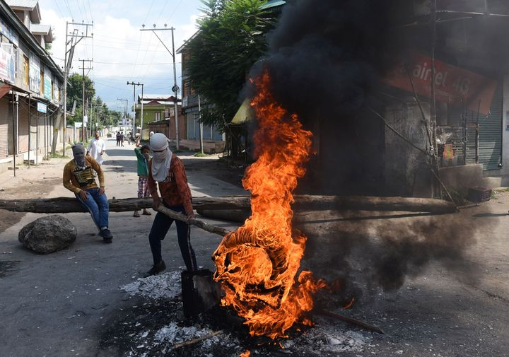 A protester holds a burning tyre near a barricade set by them to block the road during a protest against the abolishing of Article 370, on August 20, 2019 on the outskirts of Srinagar