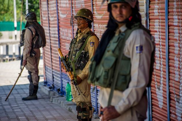 Security forces stand guard in a deserted area in Kashmir's Srinagar on August