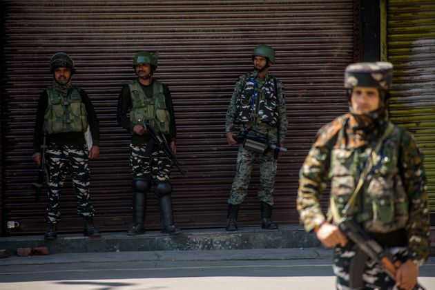 Indian paramilitary troopers stand guard in front the shuttered shops in the deserted city square of...