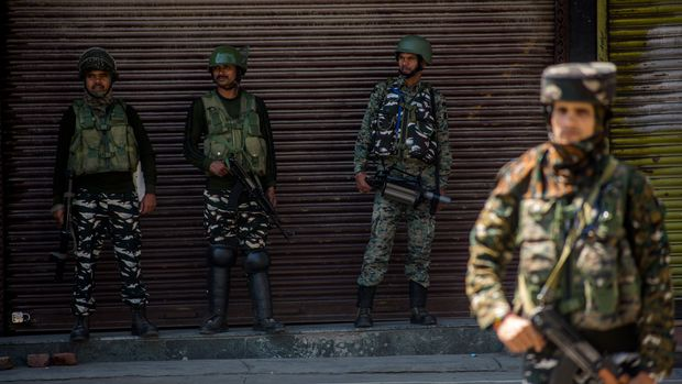 SRINAGAR, KASHMIR, INDIA - AUGUST 20: Indian paramilitary troopers stand guard in front the shuttered shops in the deserted city center, on August 20, 2019 in Srinagar, the summer capital of Indian administered Kashmir, India.  Curfew like restrictions remain in place in Kashmir for the fourteenth consecutive day after India revoked articles 370 and 35A, and phone and internet services also remained suspended. Article 35A of the Indian Constitution was an article that empowered the Jammu and Kashmir state's legislature to define permanent residents of the state and provided special rights and privileges to those permanent residents, also preventing non-locals from buying or owning property in the state. Prior to 1947, Jammu and Kashmir was a princely state under the British Empire. It was added to the Constitution through a Presidential Order. The Constitution Order 1954, (Application to Jammu and Kashmir) was issued by the President of India on 14 May, 1954 in accordance with Article 370 of the Indian Constitution, and with the concurrence of the Government of the State of Jammu and Kashmir. Kashmir has been a state under siege, with both India and Pakistan laying claim to it. Human rights organizations say more than 80,000 have died in the two decade long conflict with the Indian government claiming the number as 42,000. (Photo by Yawar Nazir/ Getty Images)