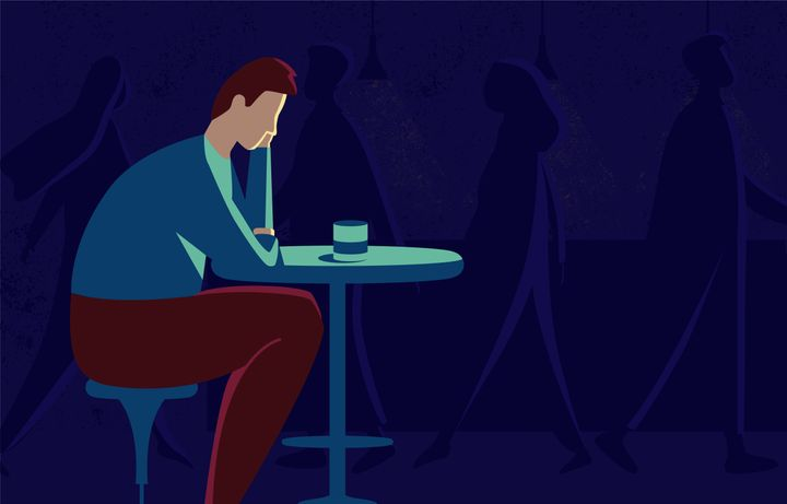 This illustration shows a sad man sitting at a table, he is in depression, the world around him has lost all color and seems faceless