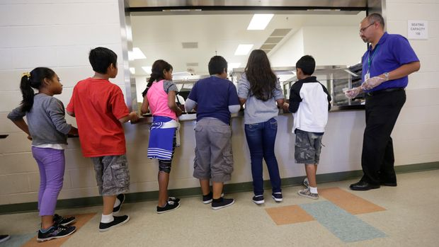 FILE - In this Sept. 10, 2014, file photo, detained immigrant children line up in the cafeteria at the Karnes County Residential Center, a detention center for immigrant families, in Karnes City, Texas. Immigrant rights activists on Friday, June 28, 2019, asked a U.S. judge to block a new Trump administration policy that would keep thousands of asylum seekers locked up while they pursue their cases, instead of giving them a chance to be released on bond.  (AP Photo/Eric Gay, File)