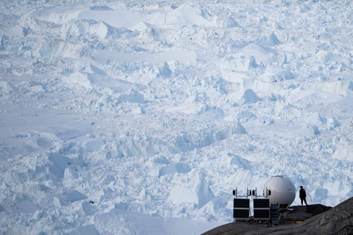 In this Aug. 16, 2019, photo, a woman stands next to an antenna at an NYU base camp at the Helheim glacier in Greenland. Summ