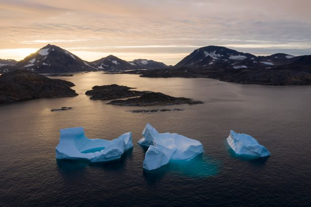 In this Aug. 16, 2019, photo, large Icebergs float away as the sun rises near Kulusuk, Greenland. Scientists...