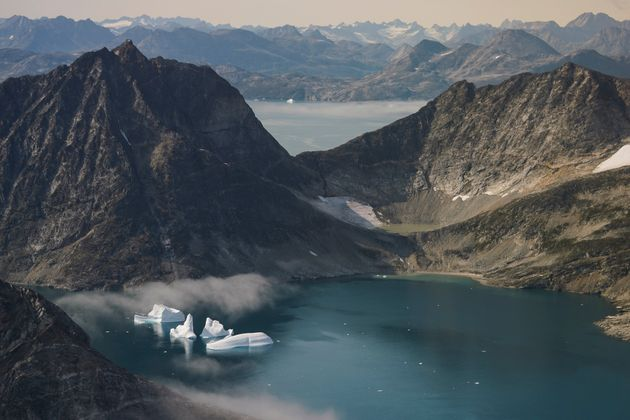 In this photo taken on Wednesday, Aug. 14, 2019, icebergs are photographed from the window of an airplane...