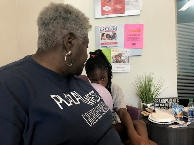 Cassandra Gentry, 67, sits with her nine-year-old granddaughter, Jada, at a back-to-school event at Plaza West, an affordable