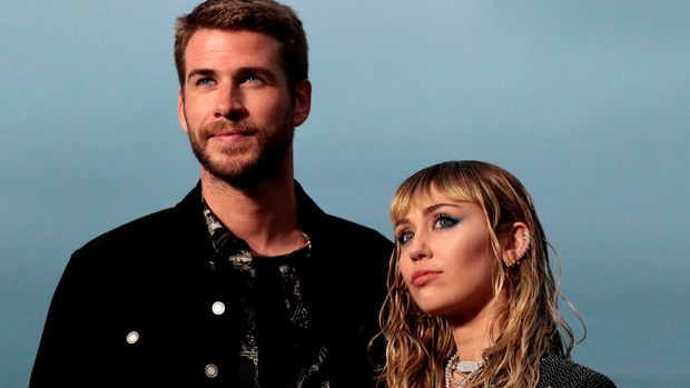 US singer Miley Cyrus and husband Australian actor Liam Hemsworth arrive for the Saint Laurent Men's Spring-Summer 2020 runway show in Malibu, California, on June 6, 2019. (Photo by Kyle GRILLOT / AFP)        (Photo credit should read KYLE GRILLOT/AFP/Getty Images)
