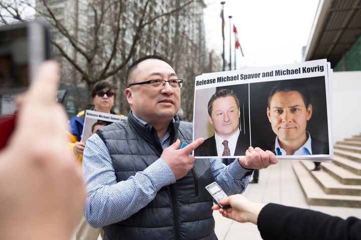 Louis Huang of Vancouver Freedom and Democracy for China holds photos of  Michael Spavor and Michael Kovrig outside British Columbia Supreme Court, in on Mar. 6, 2019