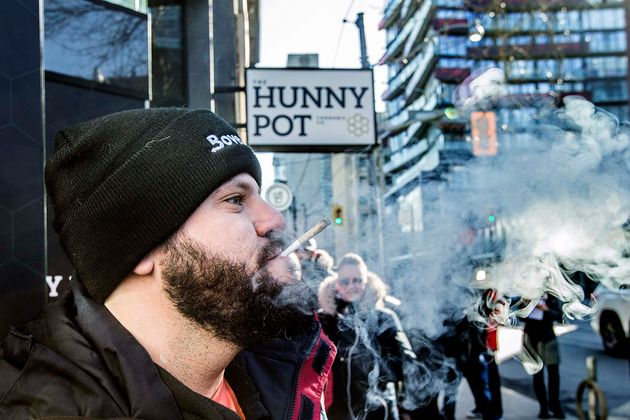 Cannabis educator Jonathan Hirsh smokes a joint he purchased outside the Hunny Pot Cannabis Co. store...