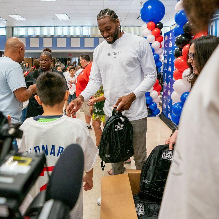 Kawhi Leonard hands out backpacks to students on Tuesday.