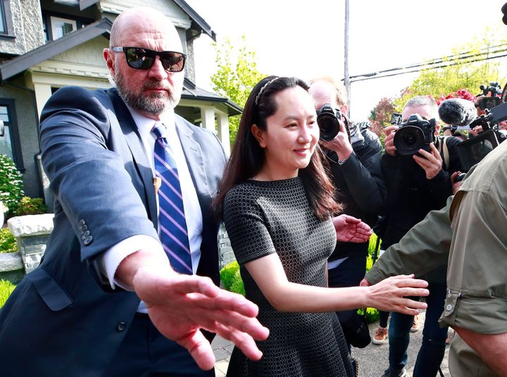 Huawei Technologies Chief Financial Officer Meng Wanzhou is escorted by security as she leaves her home on May 8, 2019 in Vancouver.