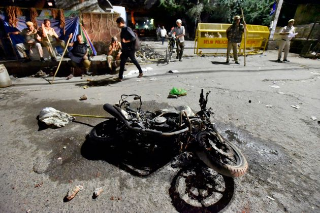 A view of the motorcycle of a Delhi police personnel that was burnt by people during the