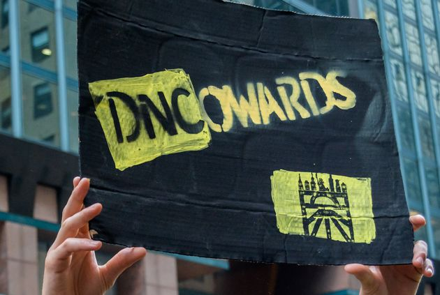 A Sunrise Movement activists holds up a sign outside the DNC