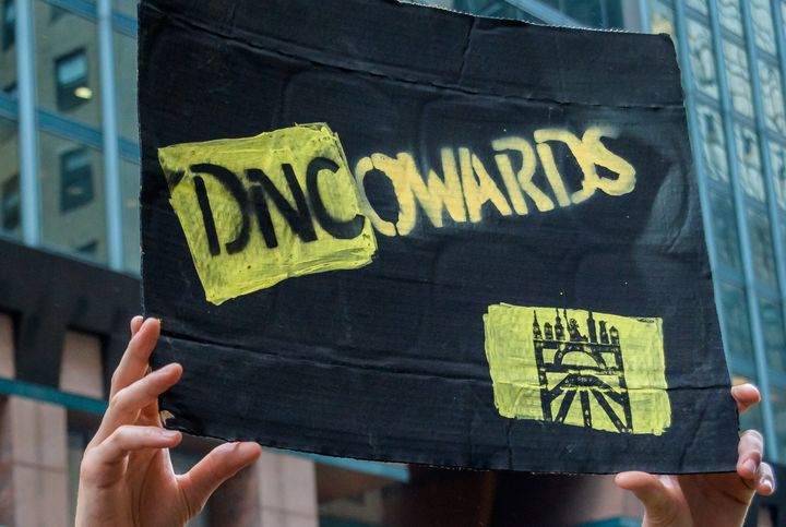 A Sunrise Movement activists holds up a sign outside the DNC headquarters.