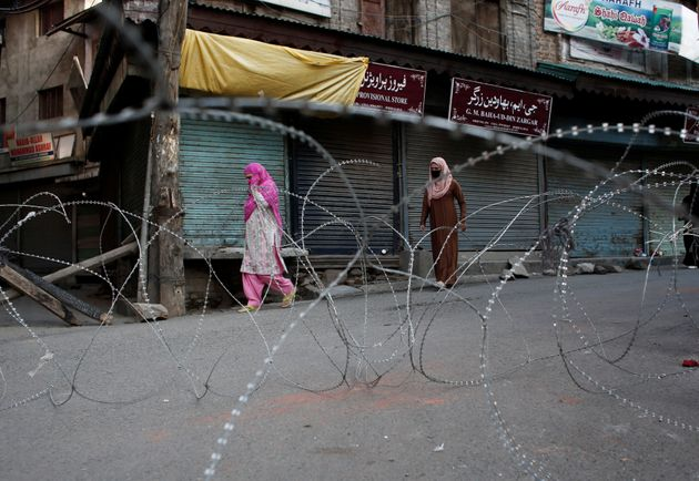 Kashmiri women walk past concertina wire laid across a road during restrictions after the scrapping of...
