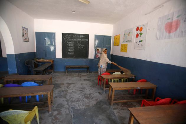 A Kashmiri school staff member cleans a deserted classroom in Srinagar on August