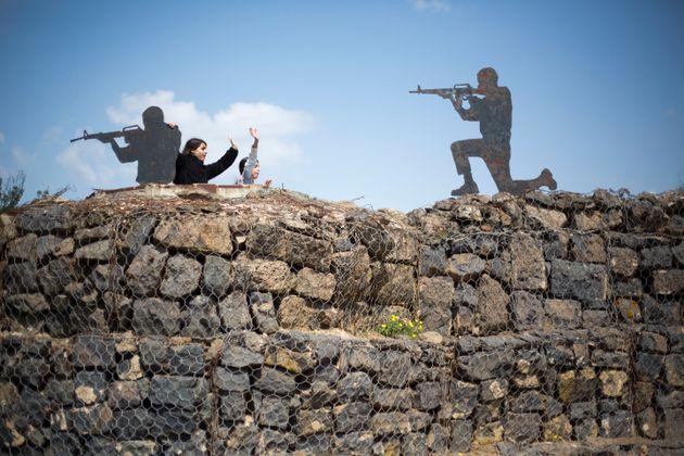 Unos turistas posan junto a soldados de metal en los Altos del Golán, ocupados por Israel a