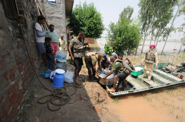 Army personnel carry food for villagers affected by severe floods, at Jamaliwala Village in Ferozpur
