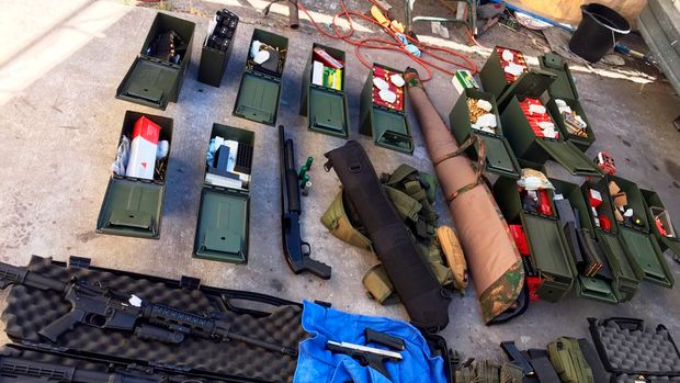 This undated photo released Wednesday, Aug. 21, 2019 by the Long Beach, Calif., Police Department shows weapons and ammunition seized from a cook at a Los Angeles-area hotel who allegedly threatened a mass shooting. Authorities say he had guns and hundreds of rounds of ammunition at his home. Rodolfo Montoya was arrested Tuesday, Aug. 20, a day after allegedly telling a co-worker at the Long Beach Marriott he planned to shoot fellow workers and others. (Long Beach Police Department via AP)
