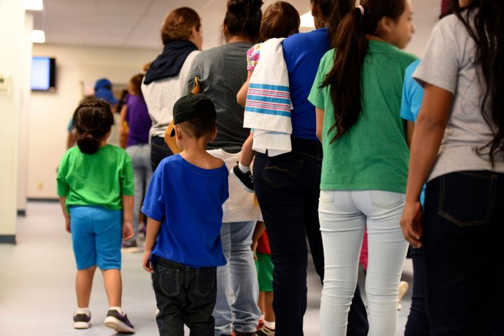 In this Aug. 9, 2018 photo provided by U.S. Immigration and Customs Enforcement, mothers and their children stand in line at