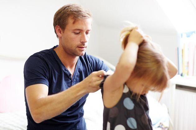 子供の髪を結う父親 イメージ写真