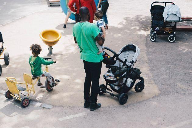 父親が子供たちと公園で遊ぶ様子 イメージ写真