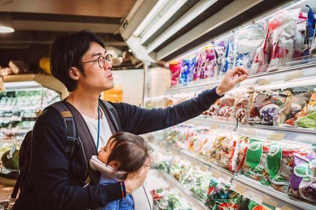 子供を抱っこしながら買い物をする父親 イメージ写真