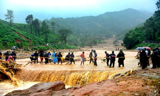 People walk through flood waters after a landslide in Meppadi, Wayanad district on August 9,
