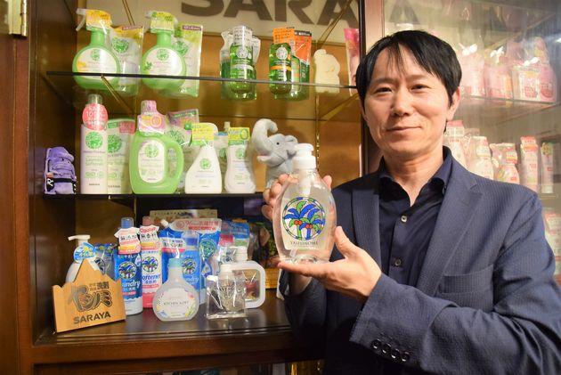 ヤシノミ洗剤を持つ広報宣伝統括部の廣岡竜也部長