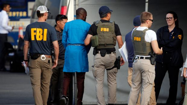 Federal agents hold a detainee, second from left, at a downtown Los Angeles parking lot after predawn raids that saw dozens of people arrested in the L.A. area Thursday, Aug. 22, 2019. U.S. authorities have unsealed a 252-count federal grand jury indictment charging 80 people with participating in a conspiracy to steal millions of dollars through a range of fraud schemes and laundering the funds through a Los Angeles-based network. The U.S. Attorney's Office says Thursday most of the defendants are Nigerian nationals. (AP Photo/Reed Saxon)