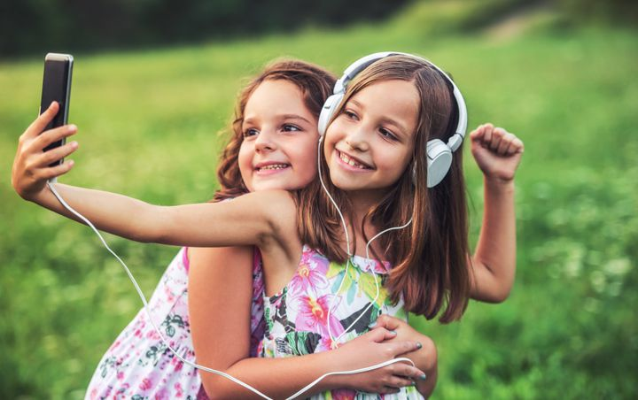 Childhood time. Cute smiling little girls enjoying in the park while making a selfie and listening to music with mobile phone