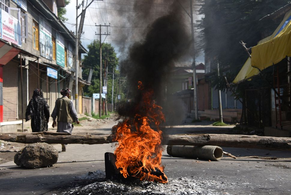 People walk past burning tires near a barricade during a protest against the abolishing of Article 370,...