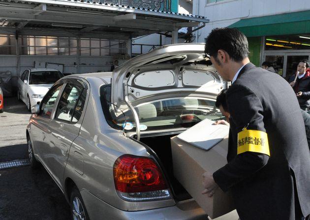 家宅捜索し、段ボール箱を車に積み込む労働基準監督署の職員ら