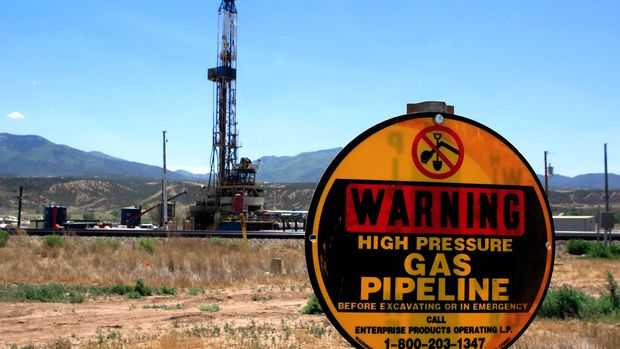 A drilling rig operates as a sign warns of underground natural gas pipelines outside  Rifle, Colorado, June 6, 2012. Picture taken June 6, 2012. REUTERS/George Frey  (UNITED STATES - Tags: ENERGY)