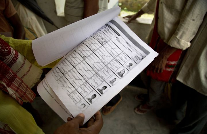 A man whose name was left out in the National Register of Citizens (NRC) draft, looks at the form he had earlier filled as he stands to receive forms to file an appeal in Mayong, 45 kilometers (28 miles) east of Gauhati, India, Friday, Aug. 10, 2018. A draft list of citizens in Assam, released in July, put nearly 4 million people on edge to prove their Indian nationality. Nativist anger churns through Assam, just across the border from Bangladesh, with many believing the state is overrun with illegal migrants.