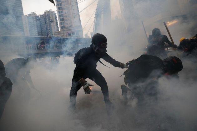 Los manifestantes, rodeados de gases lacrimógenos, durante una protesta en Tsuen Wan, en Hong...