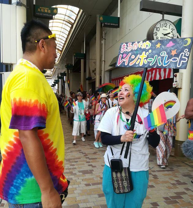 虹色のTシャツを着た矢野さん(左)に沿道で声を掛けられたパレード代表の藍川逸美さん=香川県丸亀市、2019年8月25日
