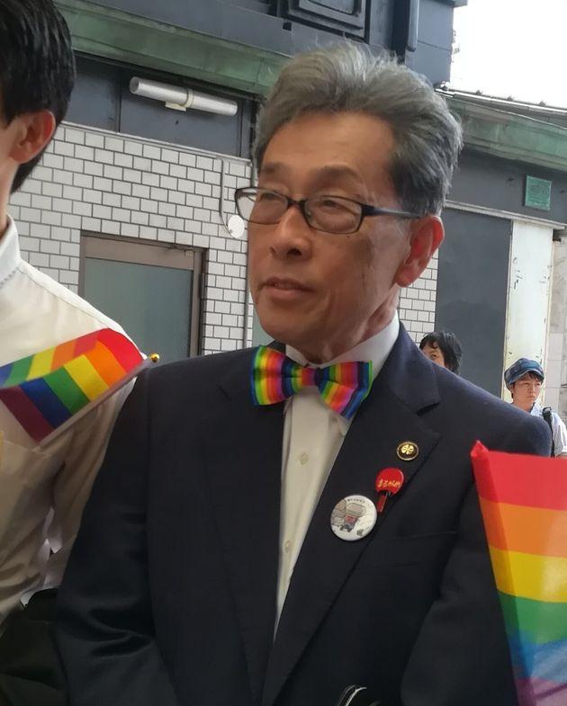 参加者にレインボーの蝶ネクタイをつけられパレードのスタート地点で写真を撮る丸亀市の梶市長=香川県丸亀市、2019年8月25日