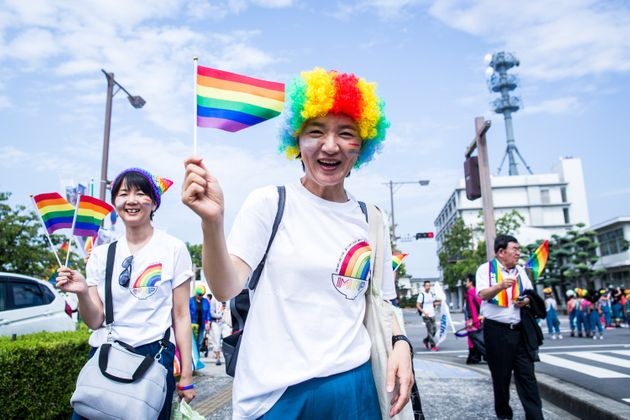 丸亀レインボーパレードで虹色の旗を振る参加者=香川県丸亀市、2019年8月25日
