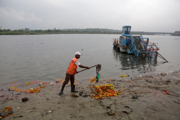 A worker removes worship materials that were thrown into the river Yamuna by devotees during the annual...