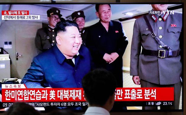 Des gens regardent une émission d'informations relatant les tirs de projectiles par la Corée...